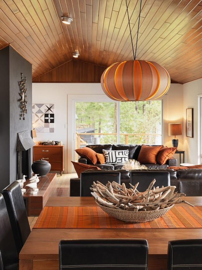 Теплые оттенки потолочного светильника, раннера на столе и аксессуаров в гостиной
