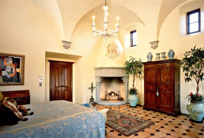 Красивый камин, украшенный лепниной, в интерьере спальни средиземноморского стиля