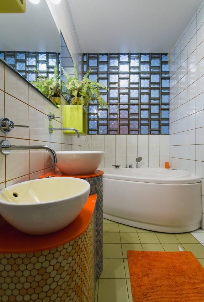 Современная небольшая ванная, где декором над угловой акриловой купелью служит светопропускающая перегородка из стеклоблоков