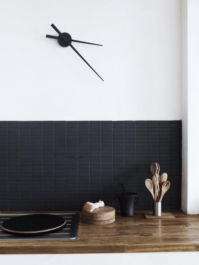 Часовой механизм, закрепленный на стене, в интерьере кухни стиля минимализм