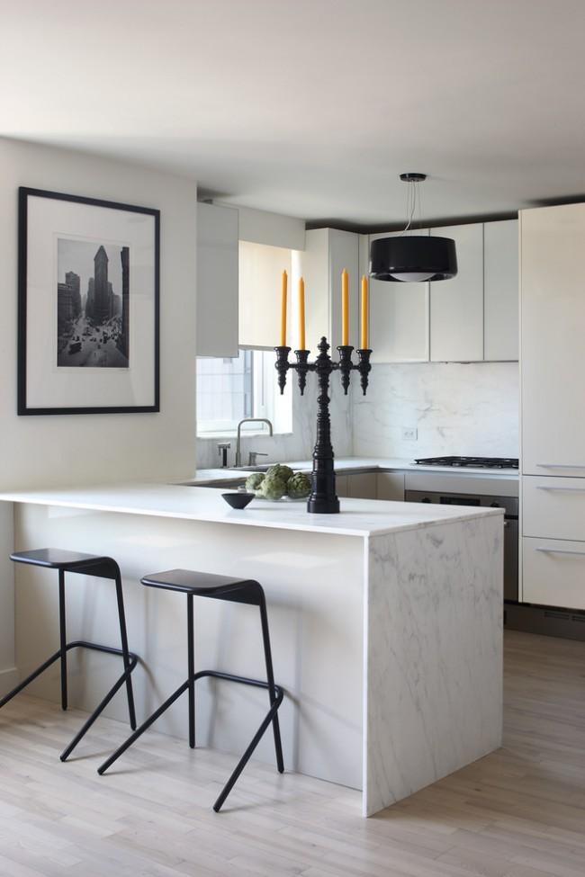 Современная кухня с преобладанием белого цвета разбавленного черными элементами. Прожилки мрамора и черно-белые фото в качестве декора дополняют картину