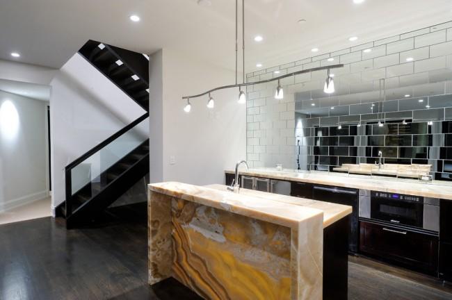 Современная кухня со стеклянным фартуком и столешницей из литьевого оникса выглядит эффектно