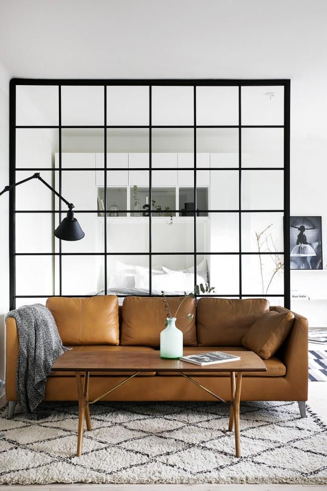 Шикарный диван на границе спальной зоны и гостиной в однокомнатной квартире