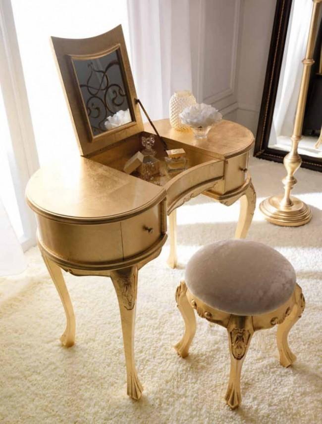 Классический небольшой туалетный столик с пуфом в золотых цветах. Кстати, еще одно достоинство откидной крышки маленького стола: элитная парфюмерия здесь не будет претерпевать губительных перепадов температуры