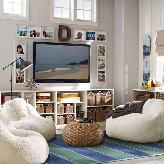 Прекрасный интерьер гостиной в пляжном стиле, где открытая система хранения под телевизором содержится в идеальном порядке с помощью плетеных корзинок