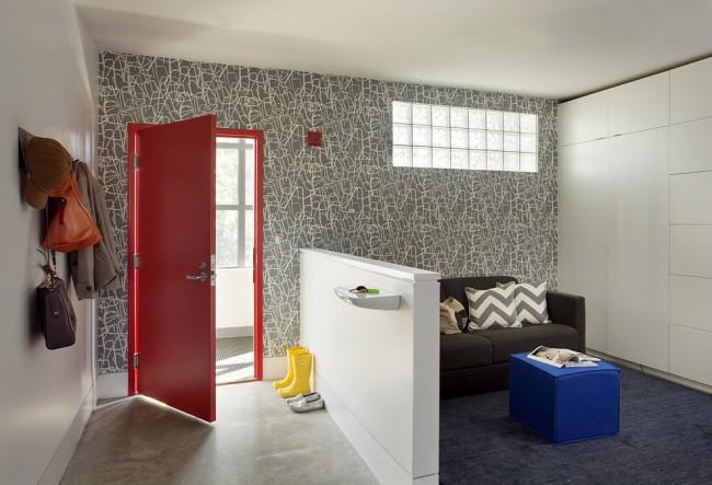 Серые обои на одной из стен в коридоре смотрятся достаточно современно в сочетании с ярко-красной дверью