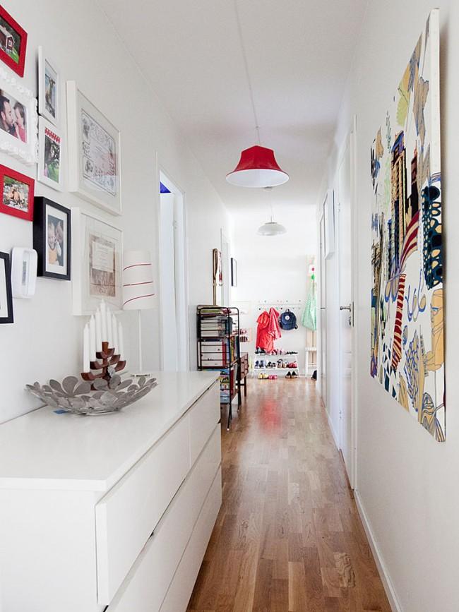 Яркие акценты в виде картин, фоторамок и плафонов в белом коридоре