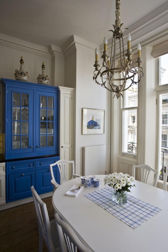 Льняные римские шторы вносят элемент разнообразия в традиционную обстановку кухонной зоны