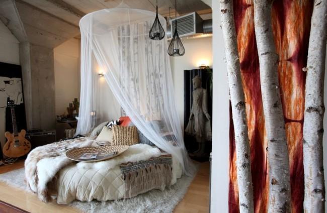 Круглая кровать с прозрачным балдахином посередине комнаты в скандинавском стиле