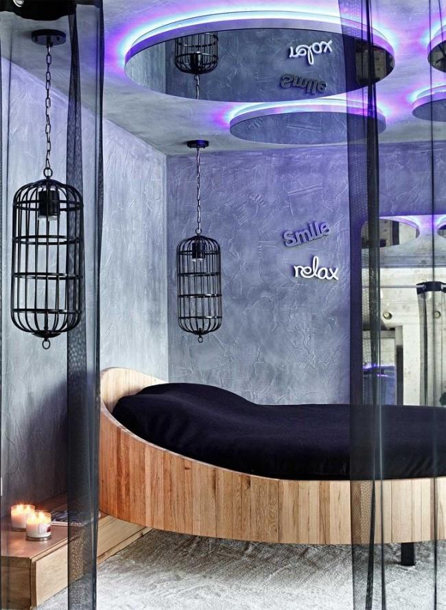 Невесомая круглая кровать в современном интерьере с обилием хрома и черненых металлических поверхностей