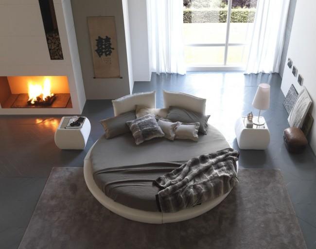 Белая круглая кровать в центре комнаты. Обратите внимание, насколько покрывала с пушистым ворсом подходят к этой мебели