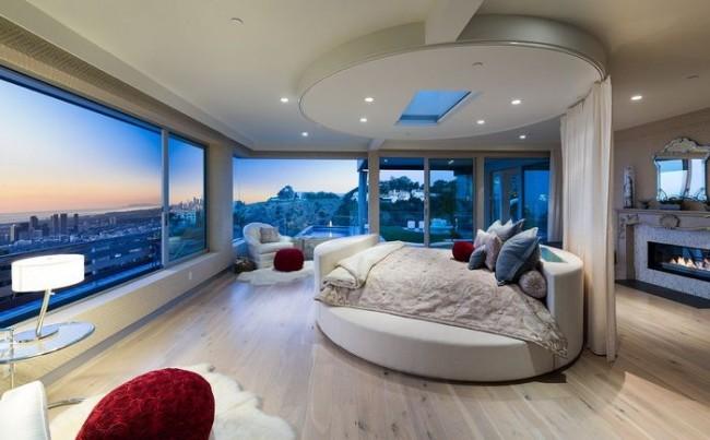 Большая круглая кровать в обширной спальне, которая не нуждается в экономии пространства