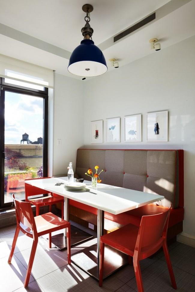 Мягкий диванчик, расположенный в углу кухни с панорамным окном