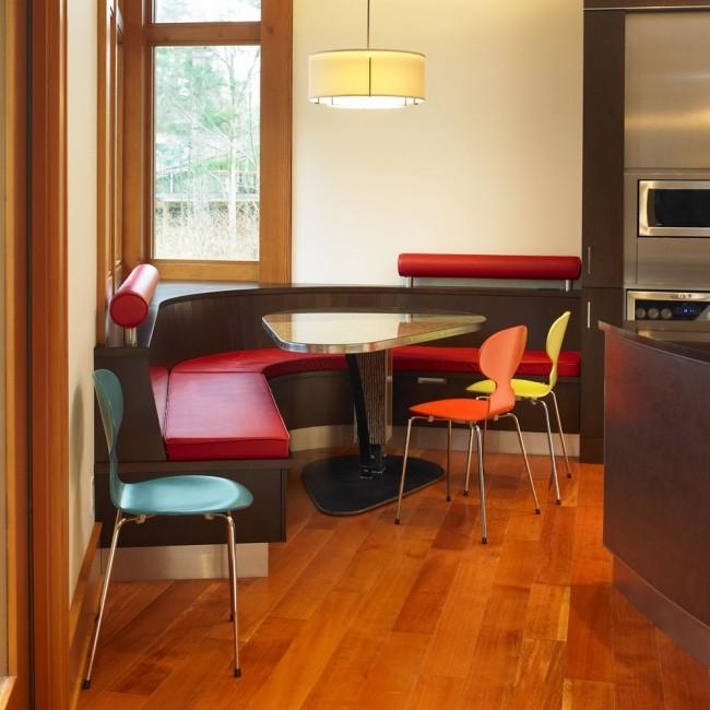 Полукруглый кухонный уголок с ярко дополненной спинкой, и легкие разноцветные стулья из металла и пластика, подходящие к динамичному современному оформлению всего помещения