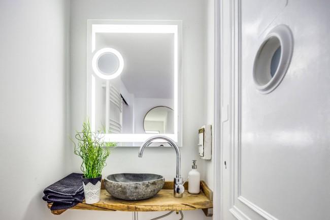 Нейтральный белый в цвете стен и подсветки - идеальный фон для демонстрации красоты натуральных материалов - дерева столешницы и камня необычной раковины
