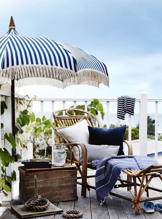 Плетеное кресло под полосатым зонтом на балконе будет как напоминание о приятном отпуске на берегу моря под лучами яркого солнца