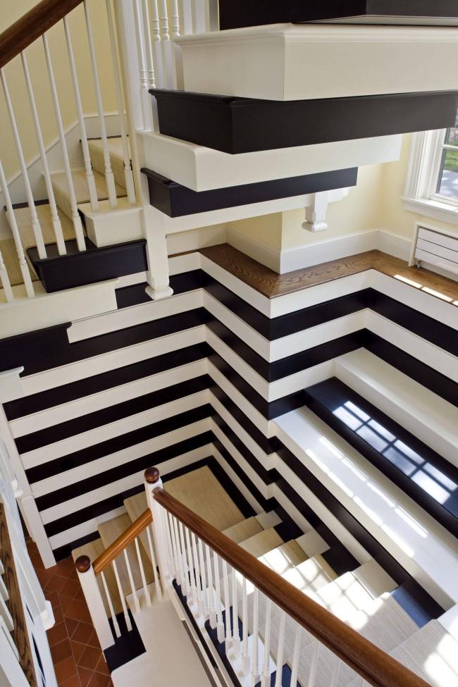 Игра с пространством лестничного пролета с помощью смелого окрашивания и черно-белых полосатых обоев
