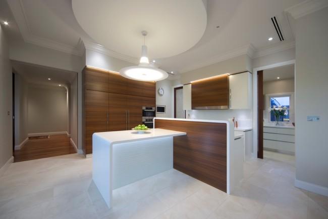 Стиль модерн в интерьере небольшой открытой кухни. Обеденная зона выделена круглой подвесной гипсокартонной конструкцией на профилях