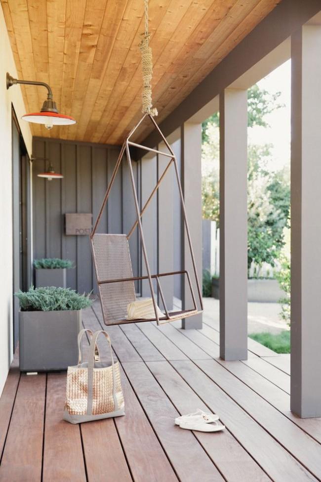Простое и практичное качающееся кресло из металлических прутьев на веранде