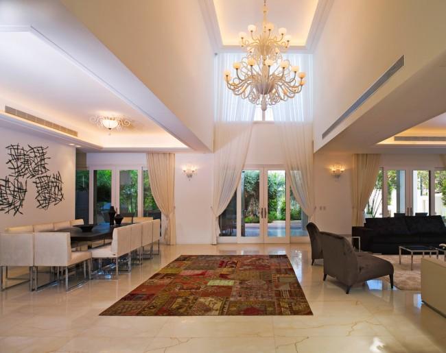 Огромная декоративная штора для окон сразу двух уровней делает интерьер холла эффектнее