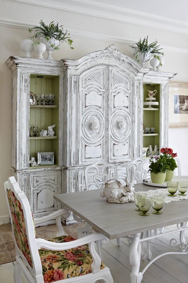 Красивый состаренный шкаф в столовой. Обратите внимание, как красиво контрастируют с белым насыщенные цвета обивки мебели