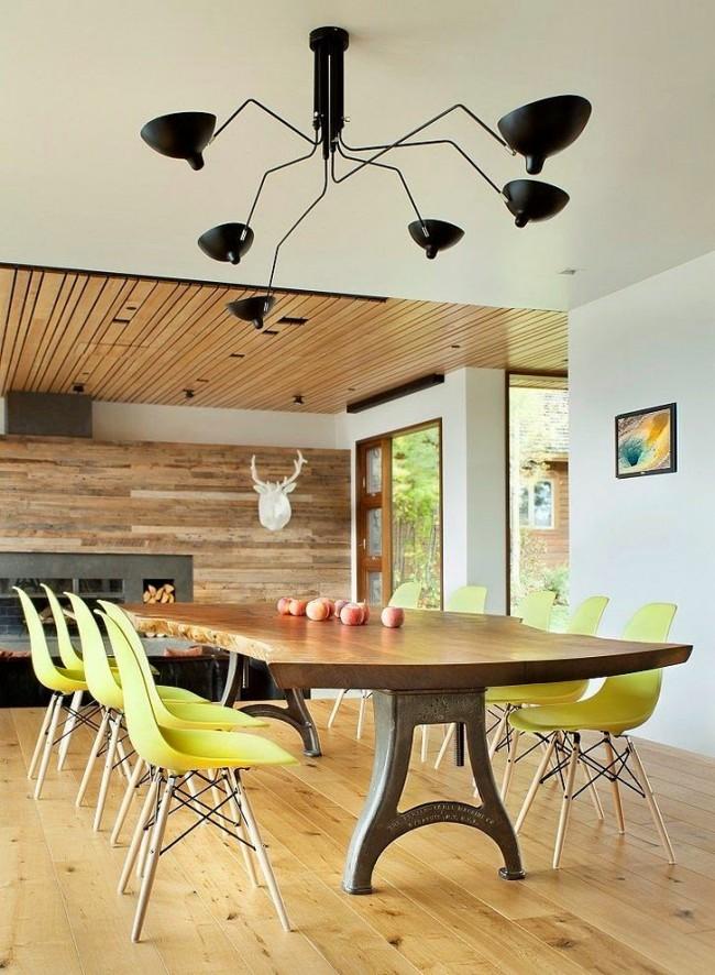 Литые ножки стола, столешница из цельного среза древесины и легендарные пластиковые стулья от Vitra