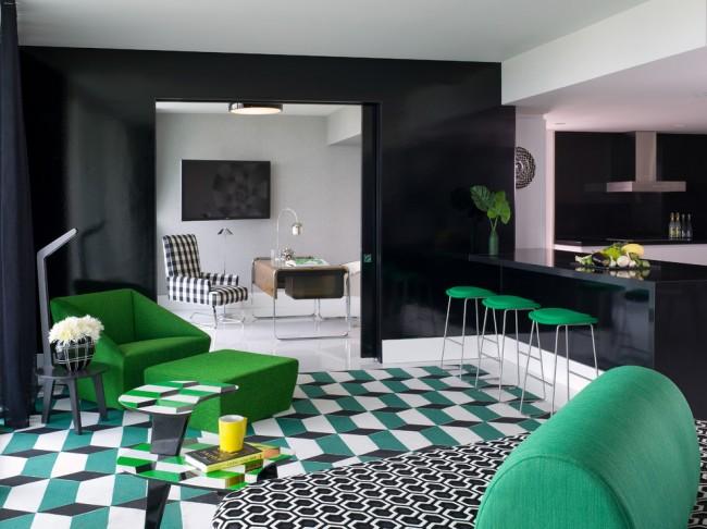 Встроенная барная стойка в интерьере большой кухни-студии в черно-белых тонах с яркими зелеными акцентами на мебели и элементах декора