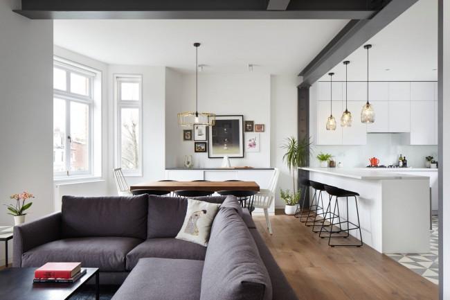 Ламинат в зоне отдыха и плитка с геометрическим орнаментом в кухонной зоне визуально разделят пространство не загромождая его