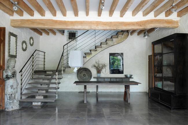 Эклектичный контраст: лестница на одном косоуре с современными перилами на фоне античного интерьера