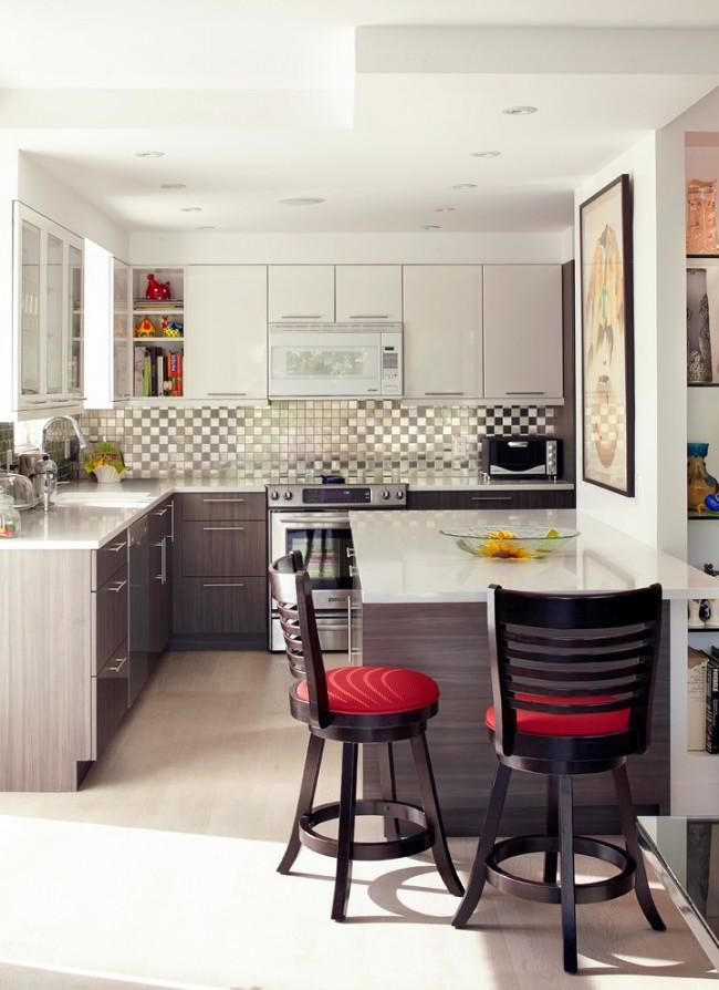 Красные акценты на обивке стульев и в некоторых элементах декора не перегружают светлую кухню-студию