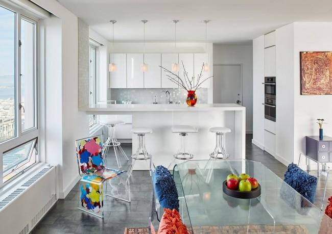 Неординарная белая кухня-студия в небольшой квартире. Яркие акценты на необычных дизайнерских стульях и мелких элементах декора интерьера выглядят очень оригинально