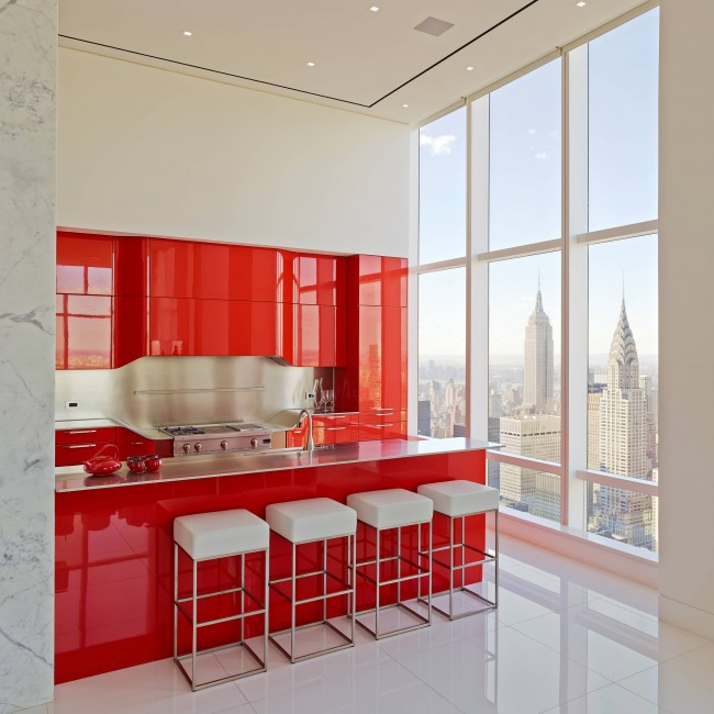 Яркий красный гарнитур акцентирует внимание на рабочей зоне кухни-студии