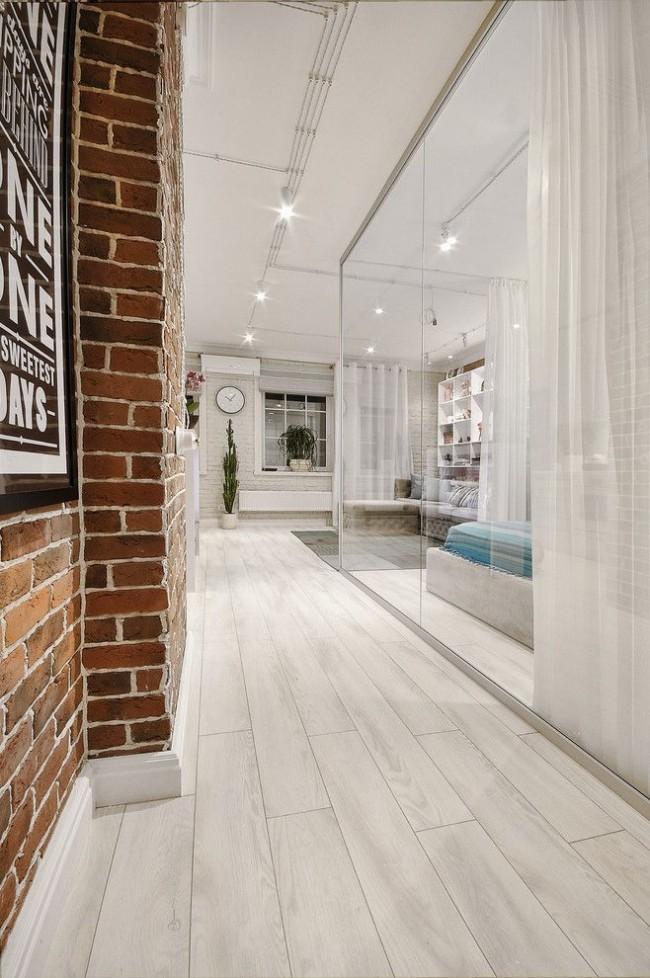 """Кирпичная коричневая стена в прихожей красиво сочетается со стеклом и белым цветом основного интерьера. Такие разновидности для имитации кладки некоторые производители называют """"лофт"""", сразу указывая рекомендованную сферу их применения в дизайне"""
