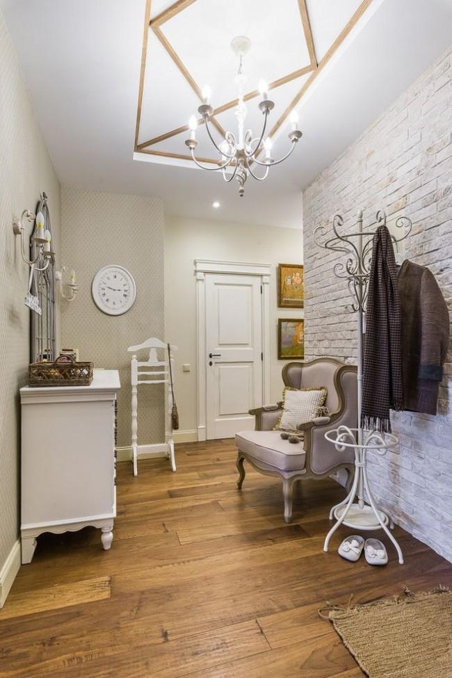 Светлая стена, имитирующая потертость и выбеленность, добавляет изюминку к современному интерьеру прихожей небольшой городской квартиры