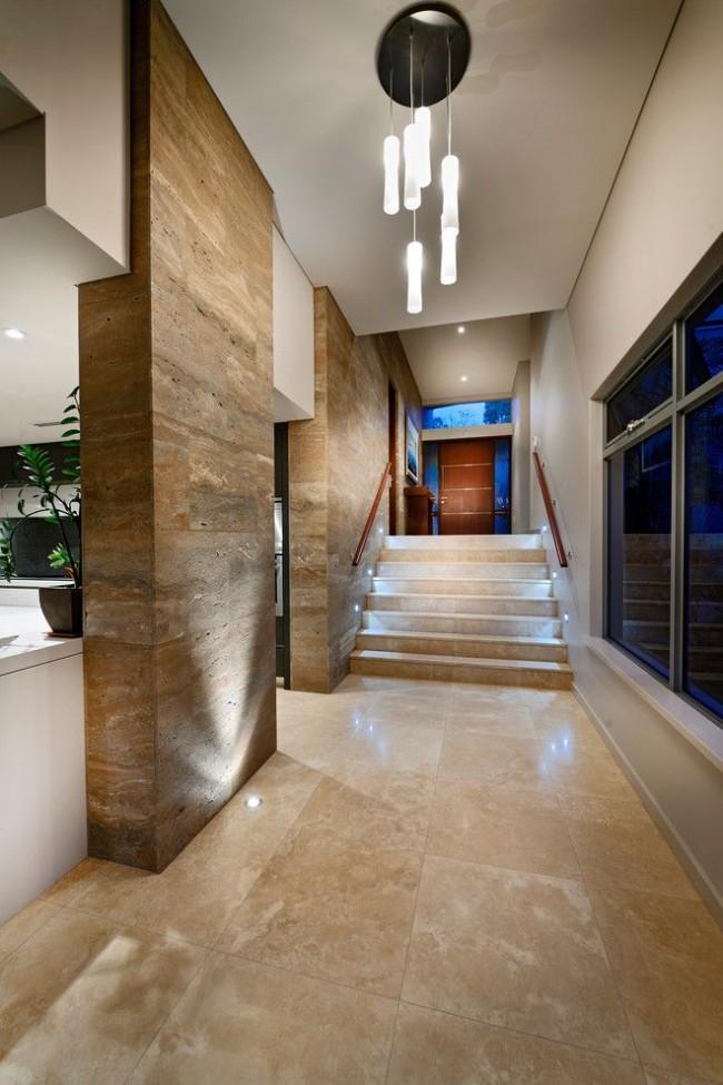Стильная прихожая со стенами, облицованными плиткой из камня и подсвеченными снизу
