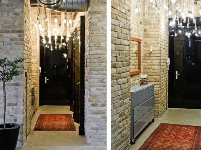 Узкая прихожая стандартной квартиры со светлыми кирпичными стенами и эффектным верхним освещением