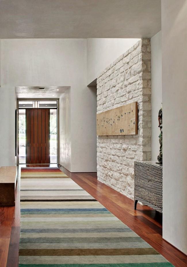Одна стена из декоративного камня является самым заметным украшением прихожей