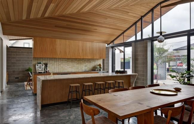 Частный стильный дом с деревянной обшивкой потолка и деревянной мебелью
