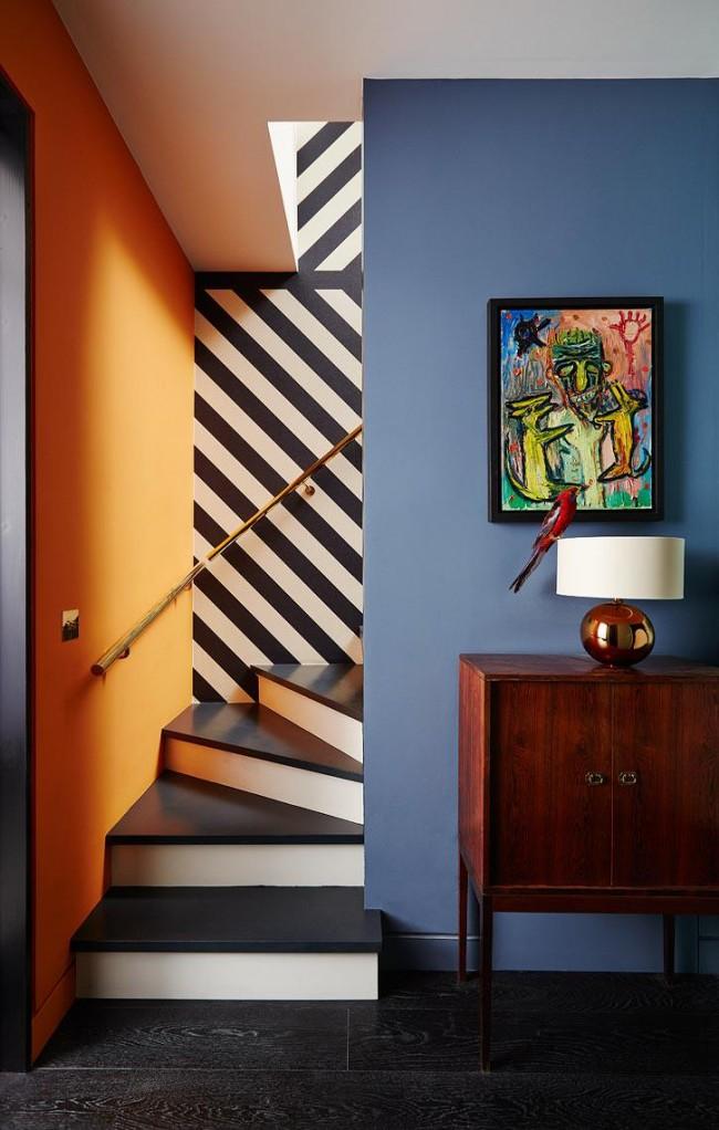 Разноцветные окрашенные стены и уводящая взгляд иллюзия, созданная полосатыми обоями над лестницей