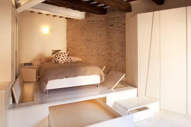 Кровать на очень большом подиуме со множеством ящиков, люков и ниш