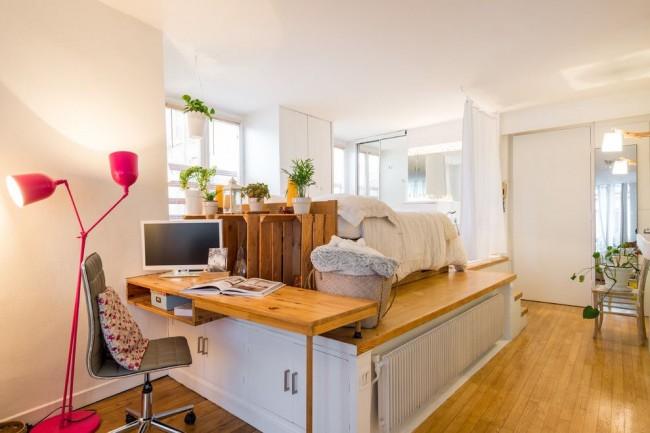 Мультифункциональный юнит, вмещающиМультифункциональный блок, вмещающий письменный стол, шкафы для хранения, спальное место и электрический радиатор отопленияй письменный стол, шкафы для хранения, спальное место и электрический радиатор отопленияинтерьер с функциональным подиумом и кроватью на нем