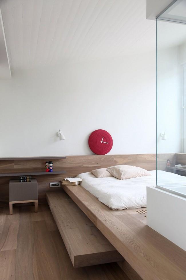 Минималистичная спальня с кроватью размещенной на подиуме