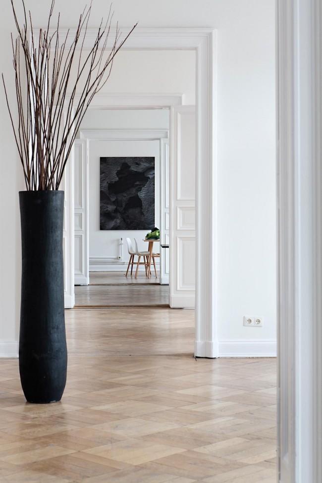Крупная ваза, окрашенная черный цвет грубой кистью, в современном интерьере