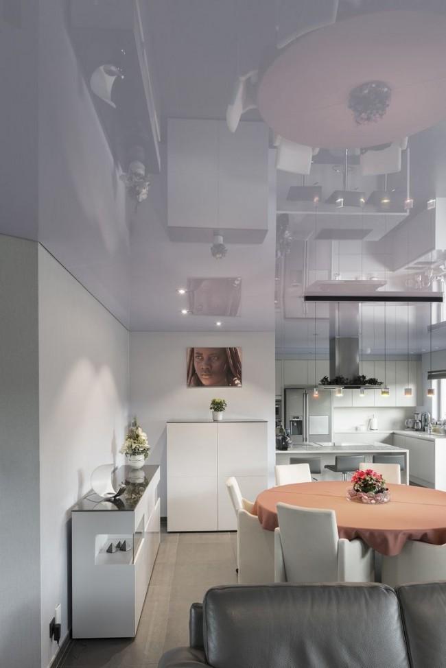 Объединенная со столовой кухня в светлом цвете и со светлым натяжным потолком