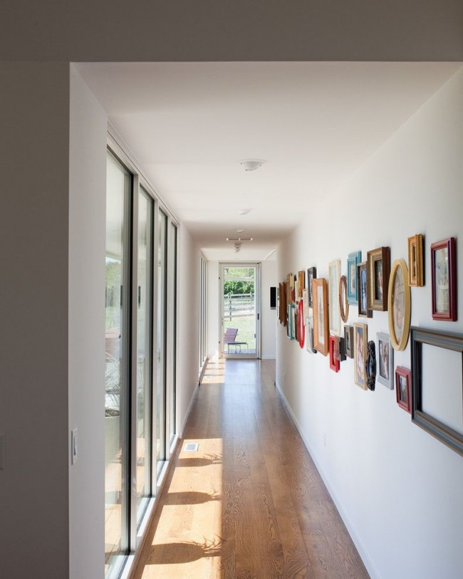 Длинный коридор частного дома с панорамными окнами и мини-галереей