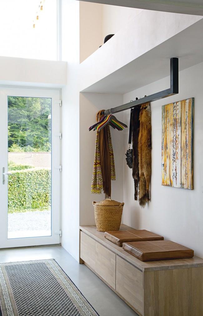 Стильная прихожая с белой пластиковой входной дверью и необычной минималистичной вешалкой