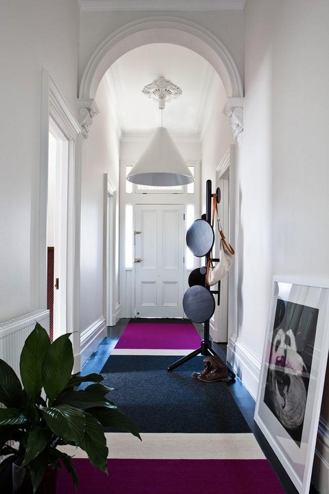 Стильный белый коридор частного дома с лаконичной люстрой и напольной вешалкой