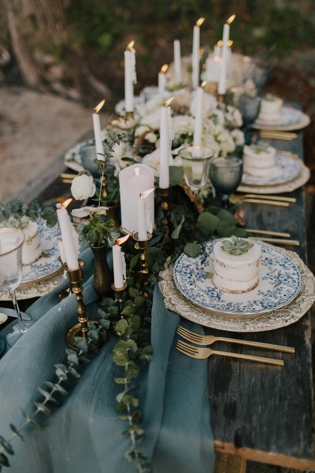 Много свечей вдоль стола и декор с помощью суккулентов