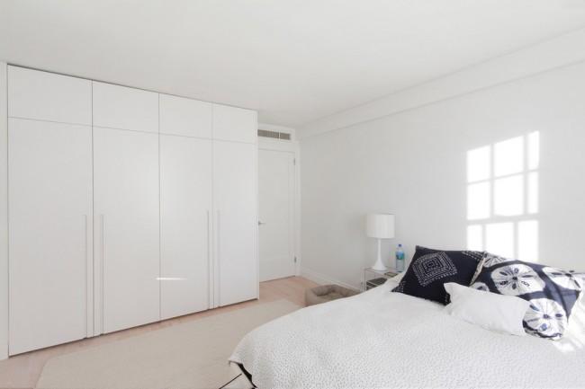 Белая спальня с вместительным корпусным шкафом с матовой поверхностью