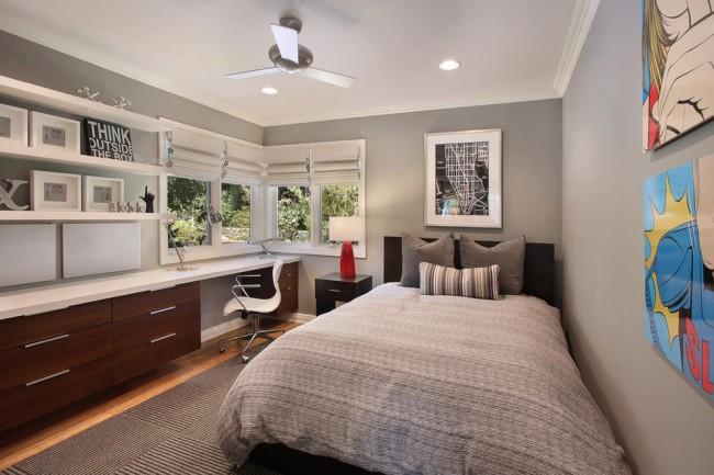 Кровать и нестандартный письменный стол у окна в комнате подростка